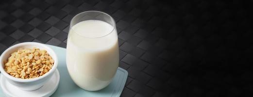 leite de soja sem açúcar adicionado em um copo em um prato de plástico de cor verde foto