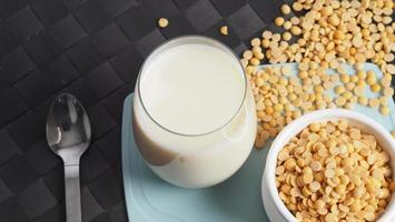 leite de soja sem açúcar adicionado em um copo em uma placa de plástico de cor verde foto