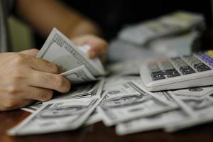 homens de negócios mulheres contando dinheiro em uma pilha de notas de 100 dólares americanos, muito dinheiro foto