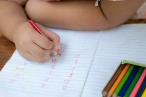 feche a mão da menina com um lápis escrevendo palavras em inglês com a mão foto