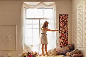 retrato de uma jovem com um vestido branco, endireitando as cortinas brancas claras perto da janela. foto
