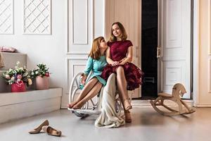uma jovem se senta em uma cadeira de balanço. perto está uma filha com um vestido festivo, uma adolescente formada. graduação na escola, faculdade. família. foto