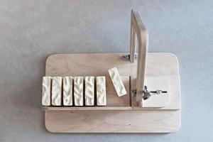 sabonete artesanal natural para bebês. sabonete já feito, cortado em pedaços em uma máquina especial. spa em casa. Pequenos negócios foto