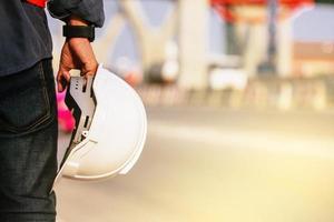 close up engenheiro segurar fundo de construção de local de capacete foto