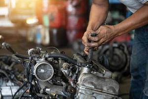 feche a mão de um homem atraente trabalhando duro e conserte o mecânico de automóveis no motor do carro na garagem de mecânicos. serviço de reparo foto