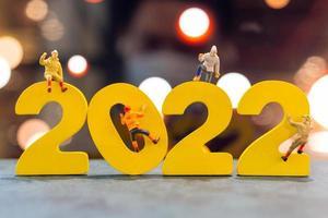 pessoas em miniatura subindo em madeira com o número 2022 foto