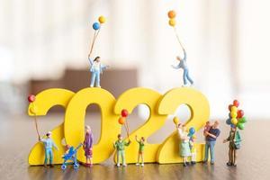 pessoas em miniatura família feliz segurando um balão no número branco 2022 foto