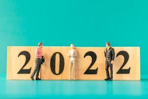 pessoas em miniatura, executivos, em pé no bloco de madeira número 2022 foto