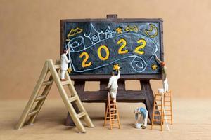equipe de trabalho de pessoas em miniatura pintando o número 2022 no quadro negro foto