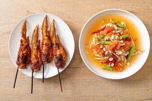 Salada picante de mamão com frango grelhado - comida de rua tradicional tailandesa foto