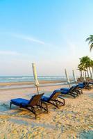 cadeira de praia vazia na praia com fundo do mar e do céu foto