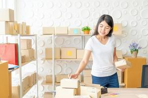 Proprietário de empresa mulher asiática trabalhando em casa com caixa de embalagem no local de trabalho - empreendedor de compras online de pmes ou conceito de trabalho freelance foto