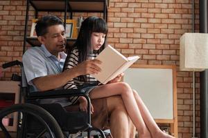 neta sentada no colo do velho avô asiático na cadeira de rodas. foto