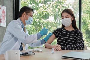 médico masculino vacinando mulher asiática para proteger covid19. foto