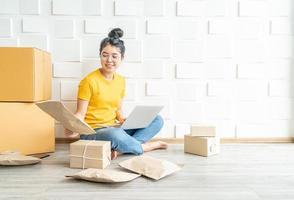 jovem empresa asiática abre proprietário de vendedor on-line usando o computador para verificar os pedidos do cliente por e-mail ou site da Web e preparar pacotes - conceito de compra ou venda on-line foto