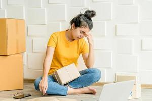 jovem mulher asiática se sentindo estressada ou deprimida na frente de seu laptop - conceito de venda online foto