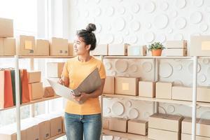 jovem mulher asiática verificando mercadorias na prateleira de estoque no armazém - venda on-line ou compras on-line conceito foto