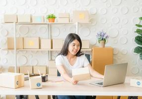 Mulher asiática se divertindo enquanto usa a internet no laptop e telefone no escritório - venda online ou conceito de compras online foto