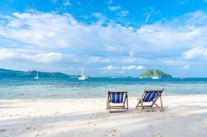 cama de praia em areia branca e mar límpido no verão foto