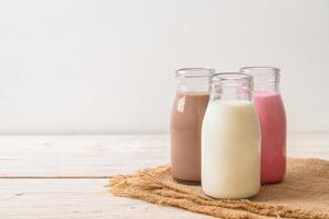 coleção de bebidas com leite com chocolate, leite rosa e leite fresco em garrafa na mesa de madeira foto