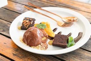 sorvete de chocolate com brownie de chocolate e banana caramelo em prato branco foto