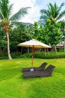 cadeira de praia vazia com guarda-chuva ao redor da piscina foto