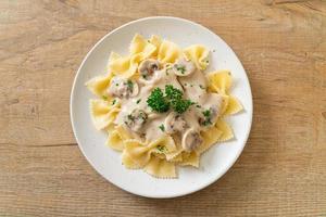 macarrão farfalle com molho de creme de cogumelos branco - comida italiana foto