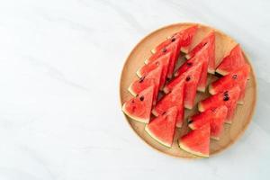 melancia fresca cortada em prato de madeira foto