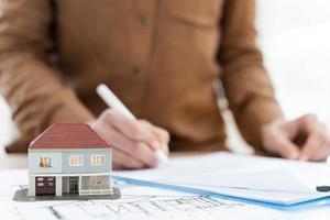 corretor de imóveis, assinando contrato de transferência de casa em miniatura. conceito de foto bonita de alta qualidade