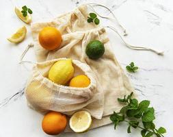 suculentas frutas cítricas maduras em sacolas ecológicas foto