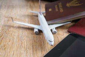 bolsa de couro e pequeno modelo de avião no fundo da placa de madeira foto