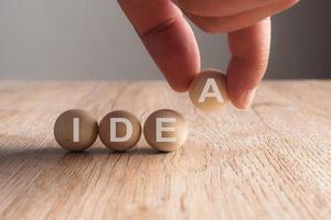 mão colocando uma palavra de ideia escrita em bola de madeira foto