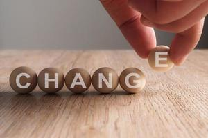 mão colocando palavra de mudança escrita em bola de madeira foto