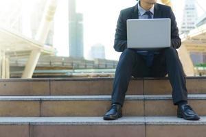 empresário sentado nas pegadas com um laptop foto