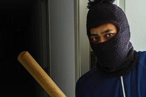 ladrão mascarado com taco de beisebol escondido atrás da porta foto
