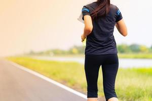 linda garota correndo na estrada, saudável fitness mulher treinando foto