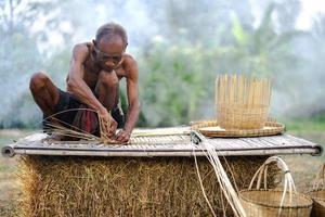 homem idoso e artesanato de bambu, estilo de vida dos habitantes locais na Tailândia foto