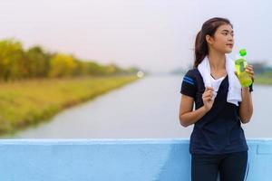 retrato de uma linda garota em roupas esportivas com uma garrafa de água foto