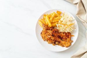 Bife de frango assado na brasa com batatas fritas foto