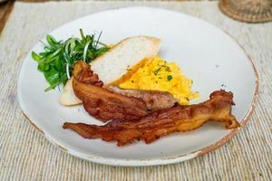 mexidos egga com bacon e salsicha no prato para o café da manhã foto