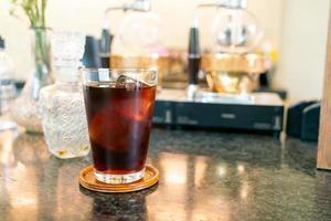 café frio ou café preto americano em vidro com cubo de gelo em cafeteria e restaurante foto