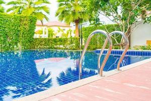 piscina com escada em lindo hotel de luxo com piscina resort foto