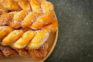 donut de açúcar em forma de espiral em placa de madeira foto