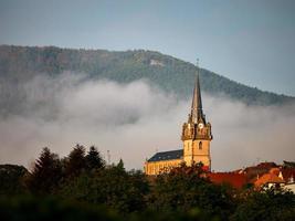 torre do sino de uma antiga igreja na aldeia de bernardschwiller na alsácia, frança foto