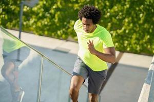 homem negro correndo lá em cima ao ar livre. jovem macho exercitando. foto