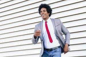 feliz empresário negro vestindo terno dançando ao ar livre. foto