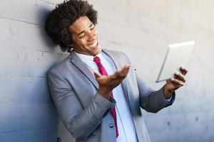 empresário negro usando um tablet digital em meio urbano foto
