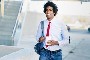 sorridente empresário negro com um copo de take-away. foto
