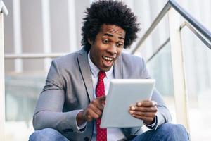 empresário negro sentado em um tablet digital foto