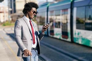 empresário negro sorridente esperando o próximo trem foto
